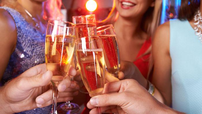 Grupp kvinnor skålar i champagne.