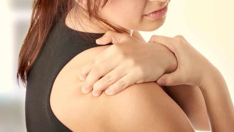 Kvinna med värk i axlarna pga fibromyalgi