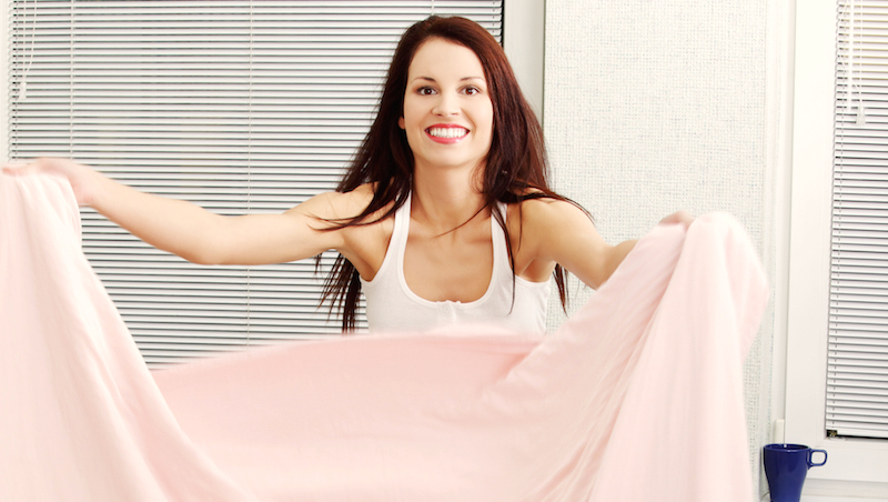 Kvinna bäddar sängen.