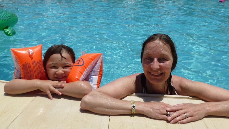 Barn med simdynor badar i poolen