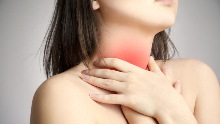 Kvinna håller om sin hals.