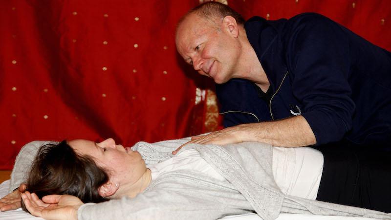 Kursledaren Lorenzo Stjernquist lägger varma händer på Denice och uppmuntrar henne att slappna av.