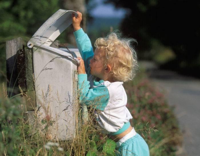 En pojke inspekterar brevlådan.