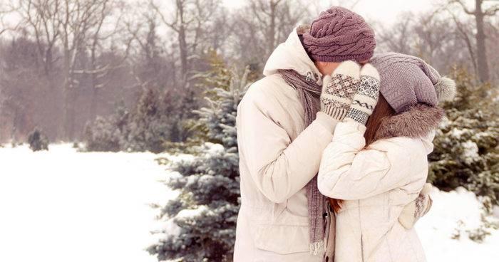 Ett par döljer en kyss med sina vantar.