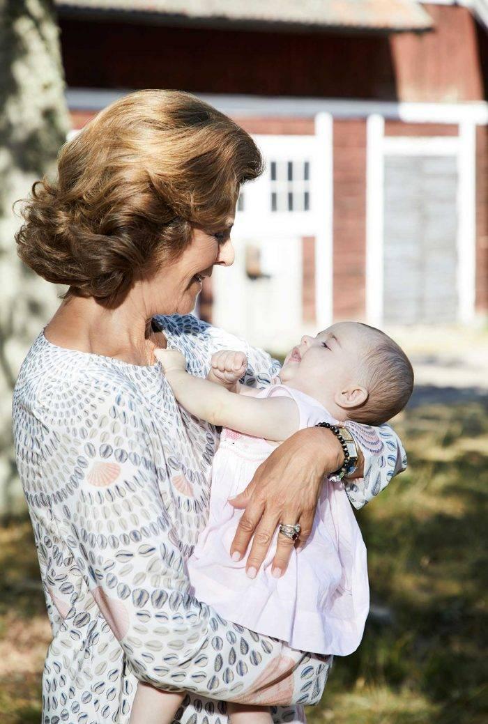 Drottning Silvia håller och gosar med prinsessan Adrienne