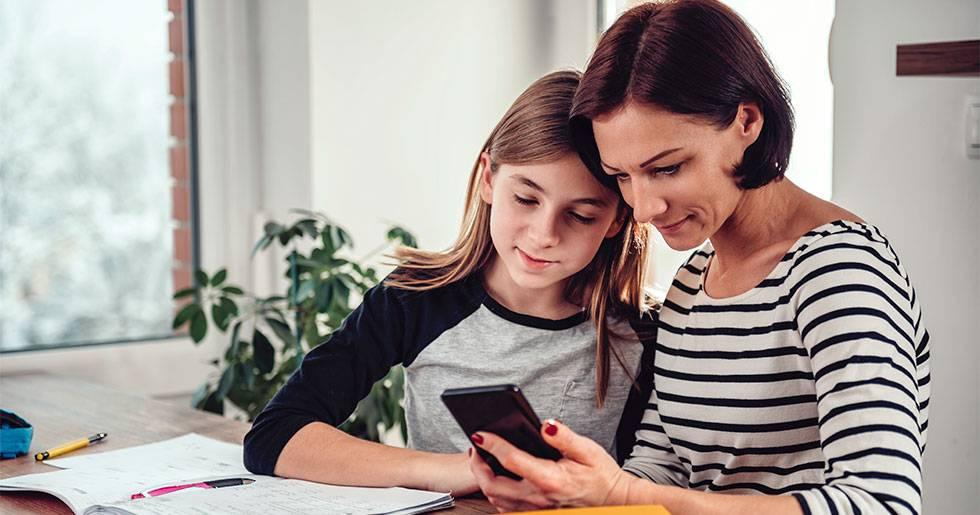 Mor och tonårsdotter tittar på en smartphone.