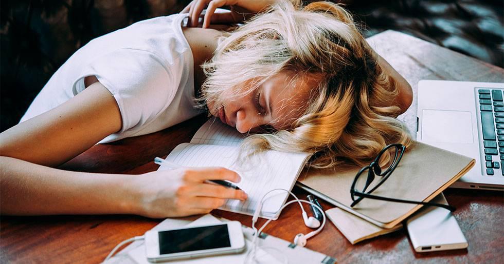 En trött tonårstjej sover på en hög böcker.