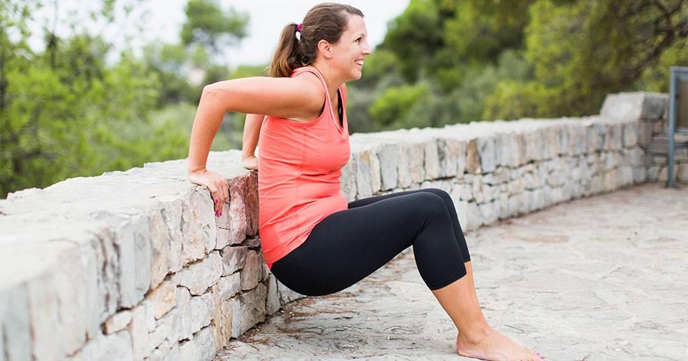 En kvinna tränar triceps mot en mur.