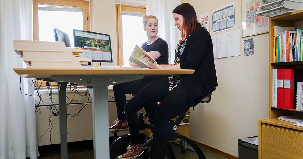 Viktoria Elmbro och Emma Wiss på kontorscyklar.