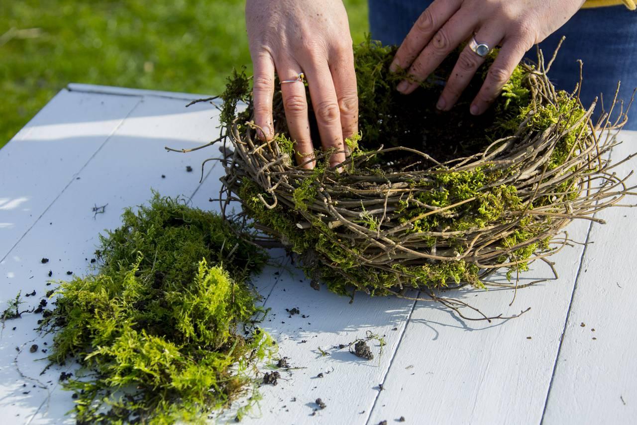 Kvinna fyller fågelbo med jord