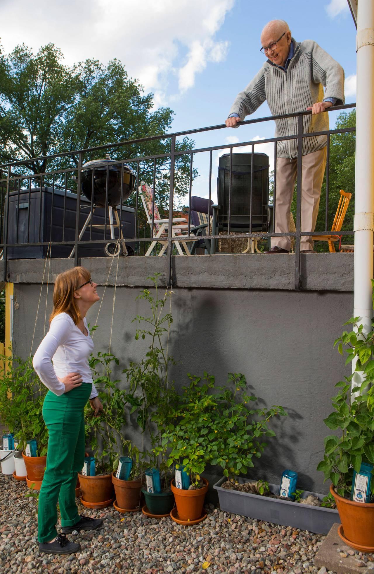 En ung kvinna tittar upp mot en balkong där en äldre man står och tittar ner mot henne.
