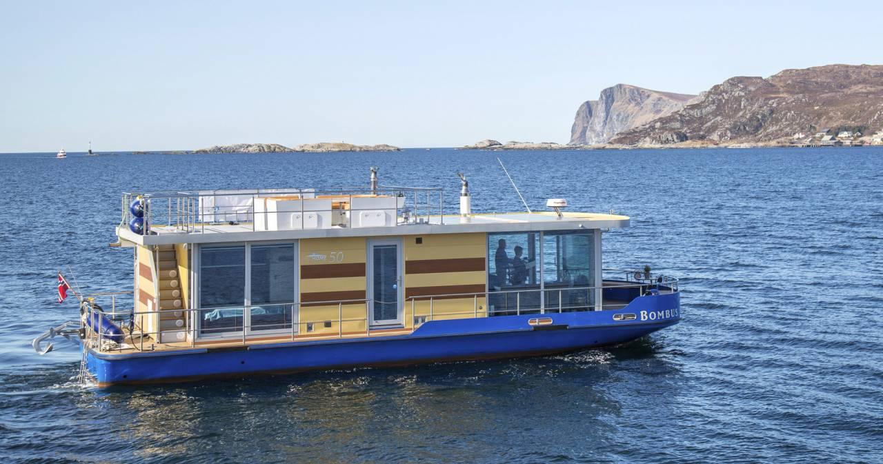 Husbåten kör på blått hav och i bakgrunden syns gråa berg
