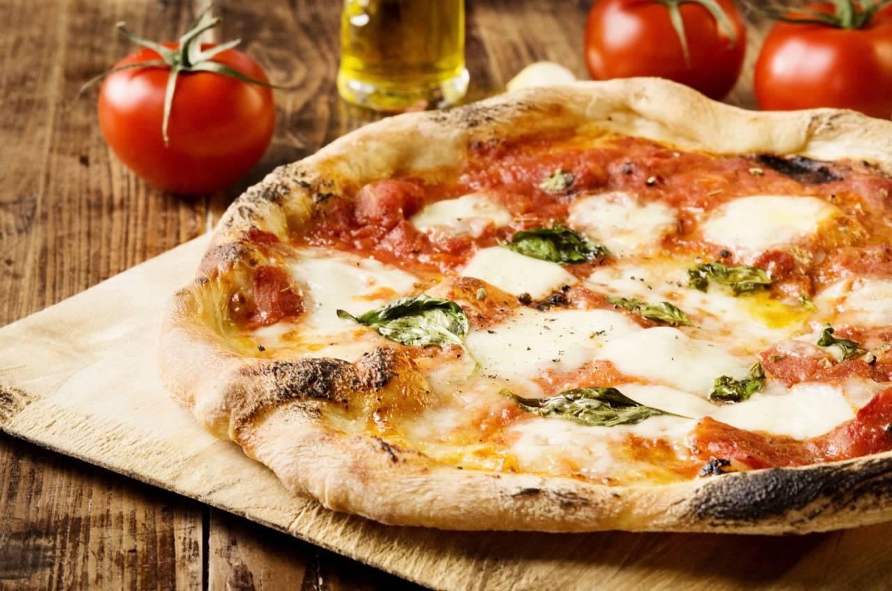 Pizza med tomater i bakgrunden
