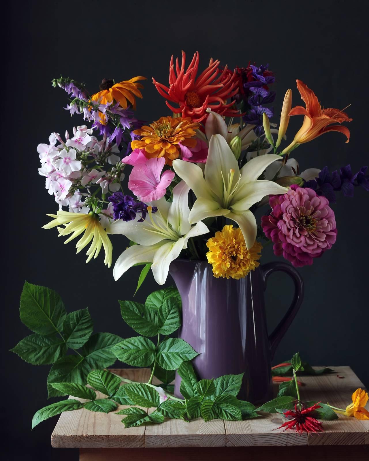 Snittblommor i starka färger i grålila vas på ett träbord