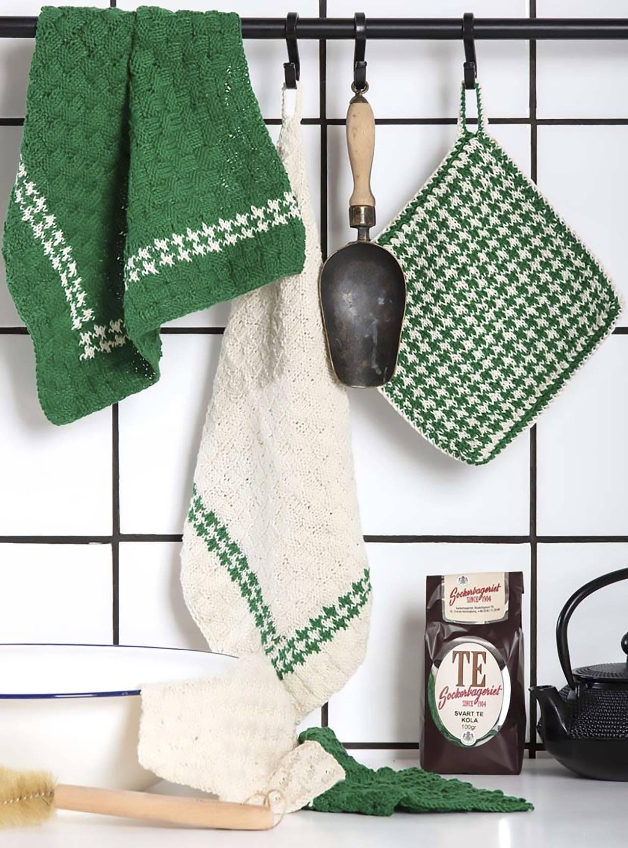 Stickade kökshanddukar, grytlappar och disktrasor hänger på rad i ett kök