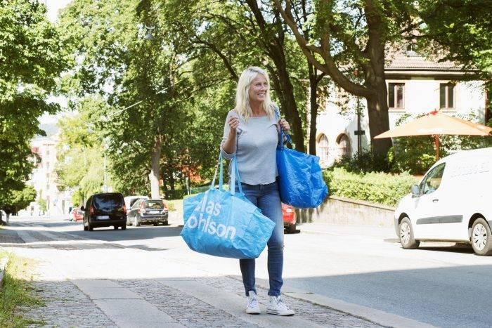 Kvinna på gata med två fullpackade blå plastkassar, en från Ikea och en från Clas Ohlson.