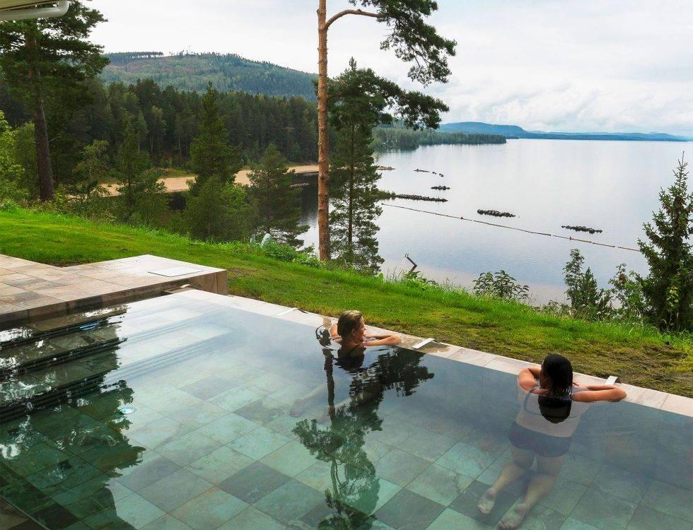 En blank pool utomhus med två personer som blickar ut över den blanka sjön Ljusnan.