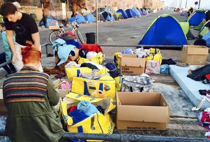 Volontärer delar ut kläder, mat och vatten till behövande. Flyktingar campar i tält på gatan framför.