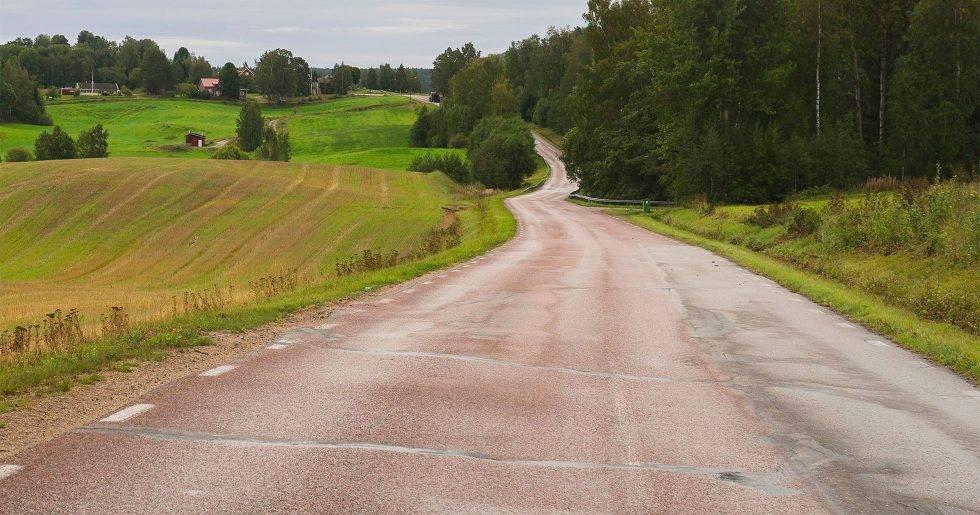 En landsväg som ringlar fram genom ett sommarlandskap.