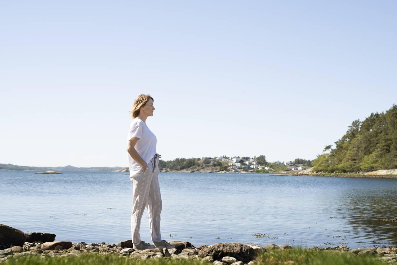 AnnCherie står vid vattnet och tittar ut över naturen
