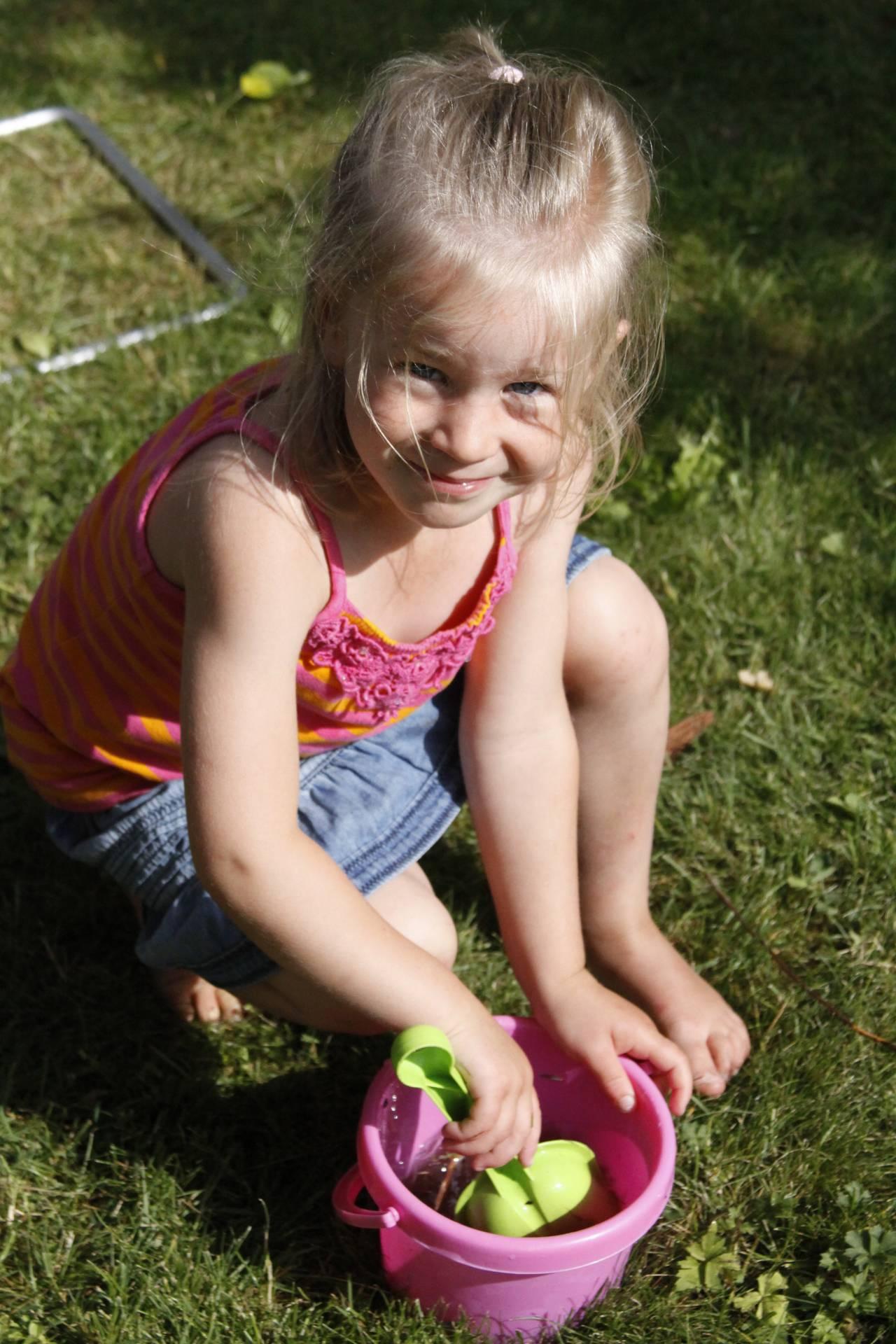 Carolinas dotter Anna leker på gräsmatta