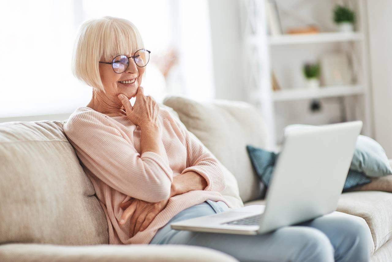 Kvinna sitter i soffan och surfar på sin dator