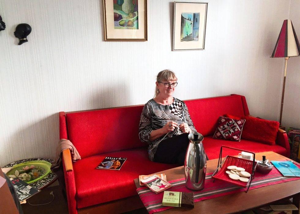 Monica Galle sitter i en röd soffa och stickar i en lägenhet inredd i 1960-talsstil.