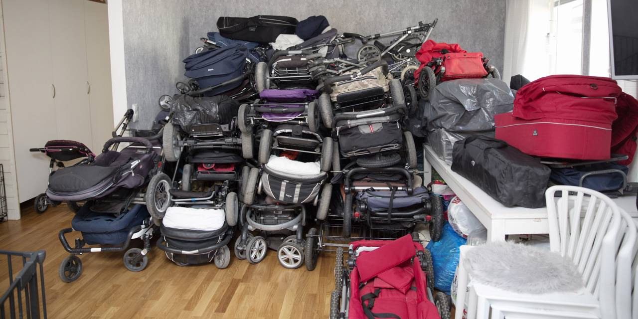 Insamlade barnvagnar ligger i en hög på golvet