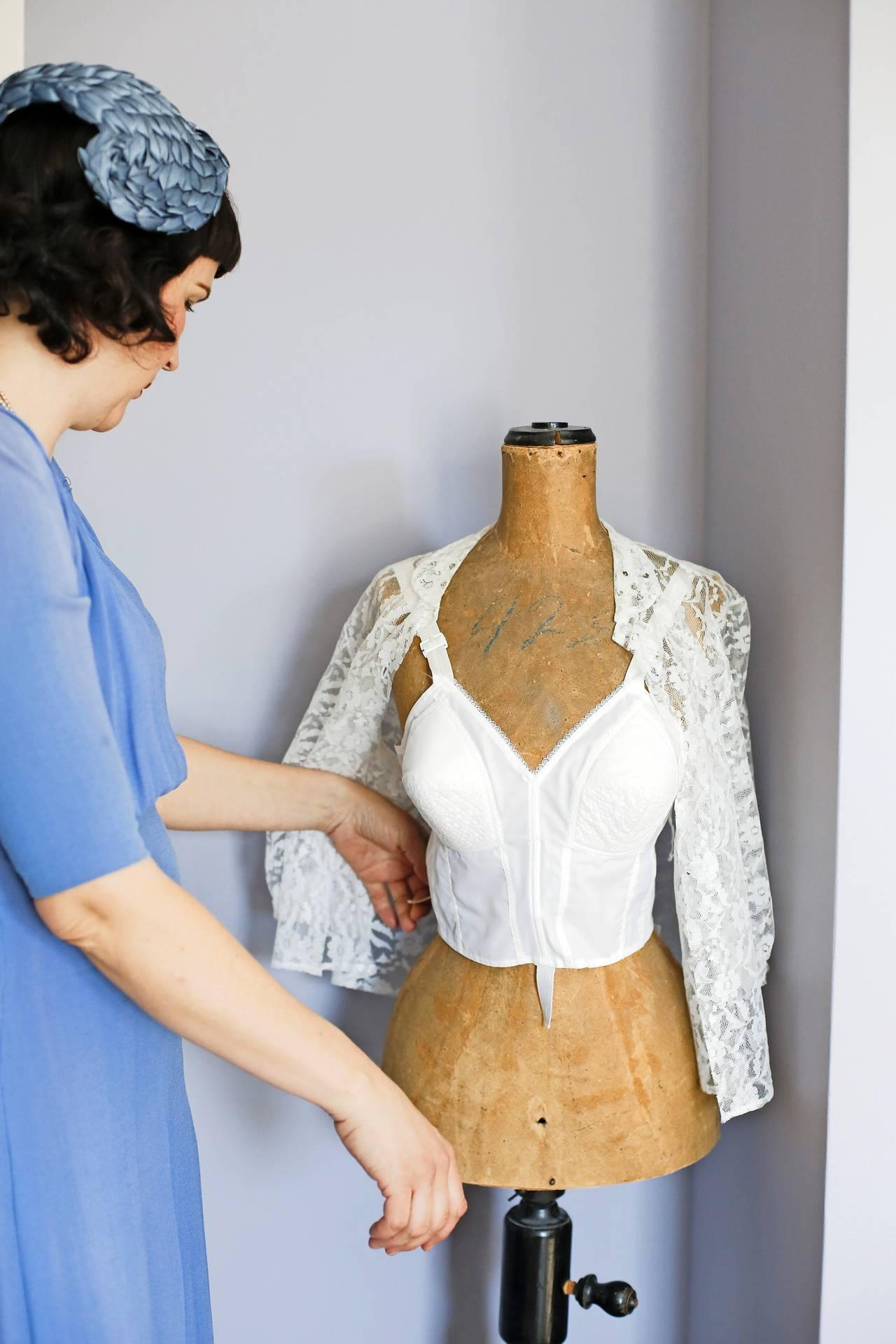 Linda inspekterar en provdocka med retrokläder
