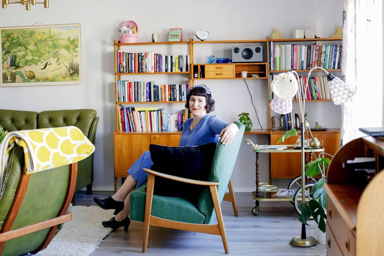Linda sitter I en fåtölj i sitt vardagsrum som även det är inrett i vintagestil.