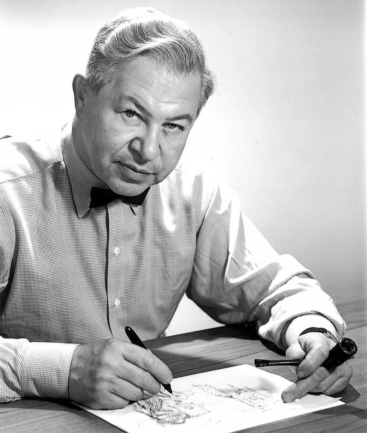 Arne Jacobsen, arkitekter och formgivare, skissar i ett block och tittar in i kameran