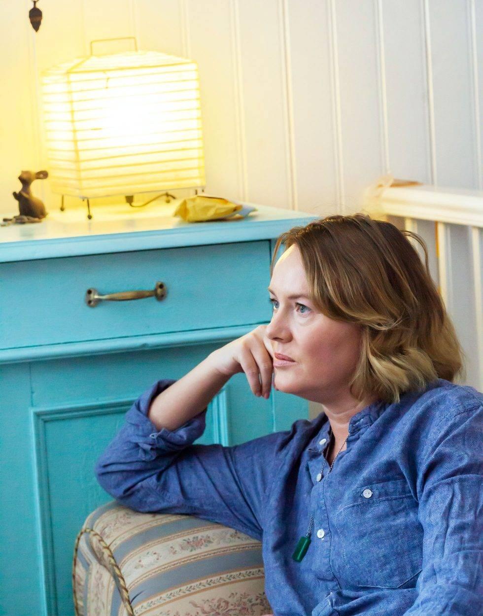 En kvinna i 45-årsåldern sitter och tänker.