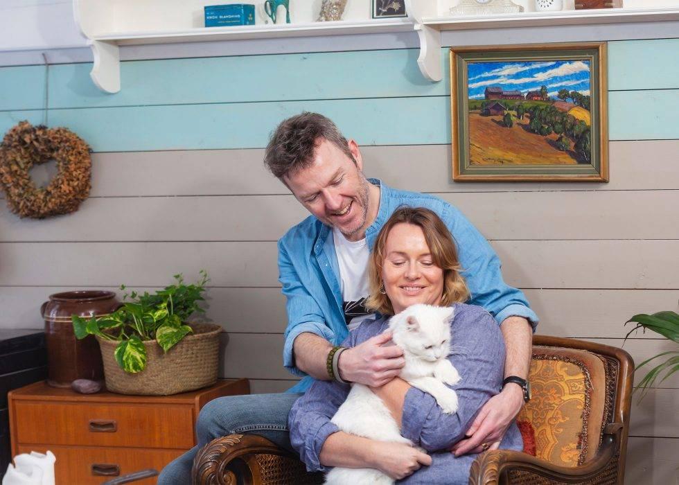 En kvinna i 45-årsåldern sitter med en katt i knät och hennes make bakom sig.