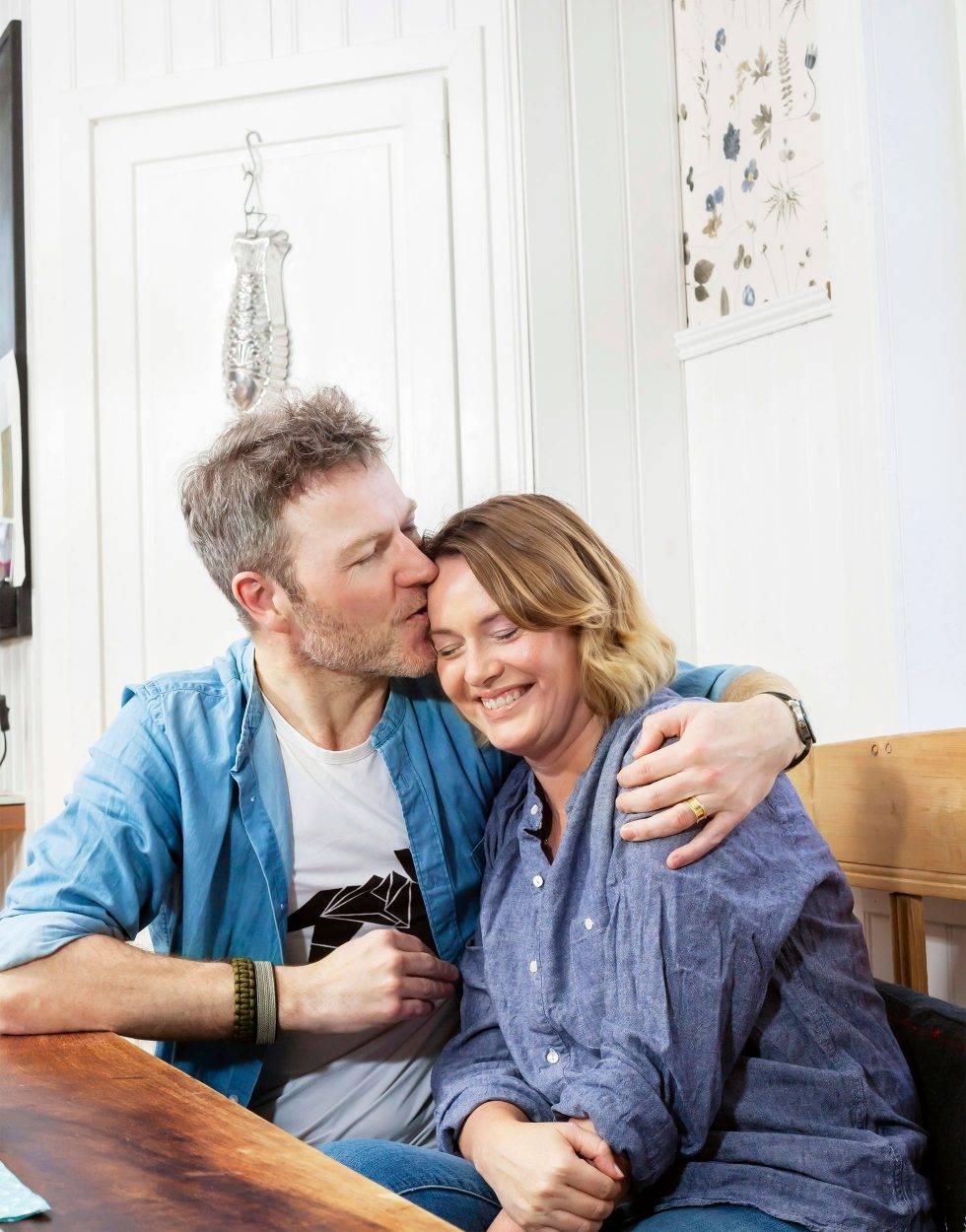 En man i 45-årsåldern håller om sin fru och kysser henne på pannan.