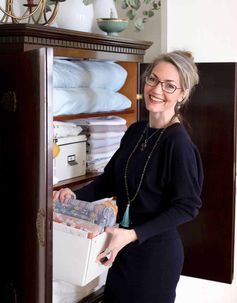 En kvinna i medelåldern bär ut saker ur ett linneskåp.