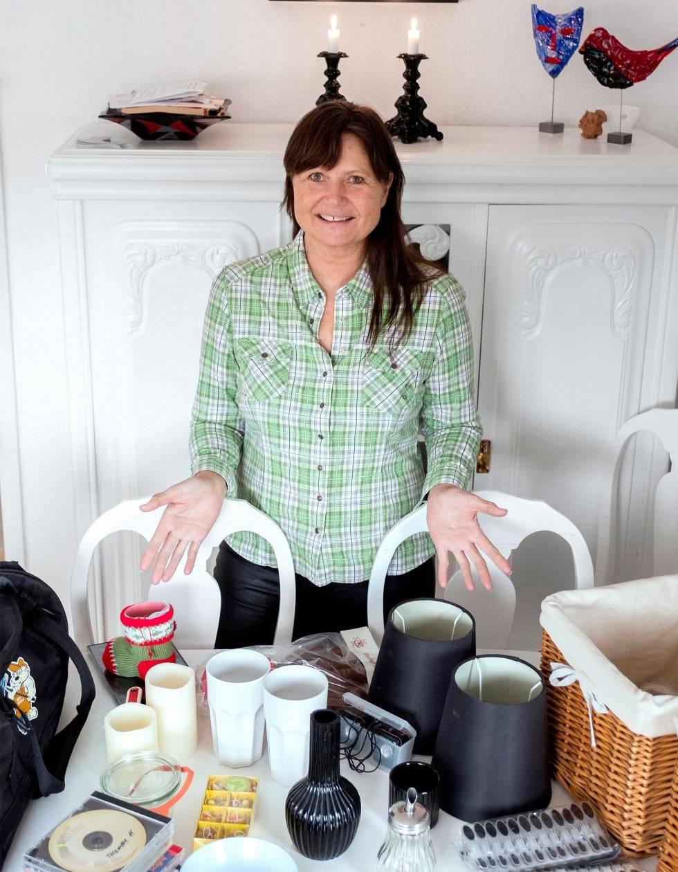 En medelålders kvinna står framför ett bord med porslin och andra prylar.
