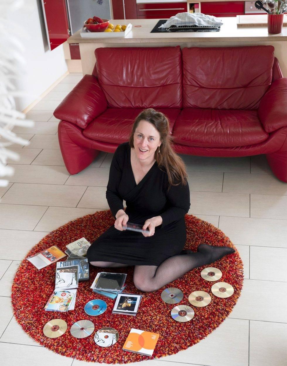 En medelålders kvinna med brunt hår sitter på en matta med cd-skivor utspridda kring sig.