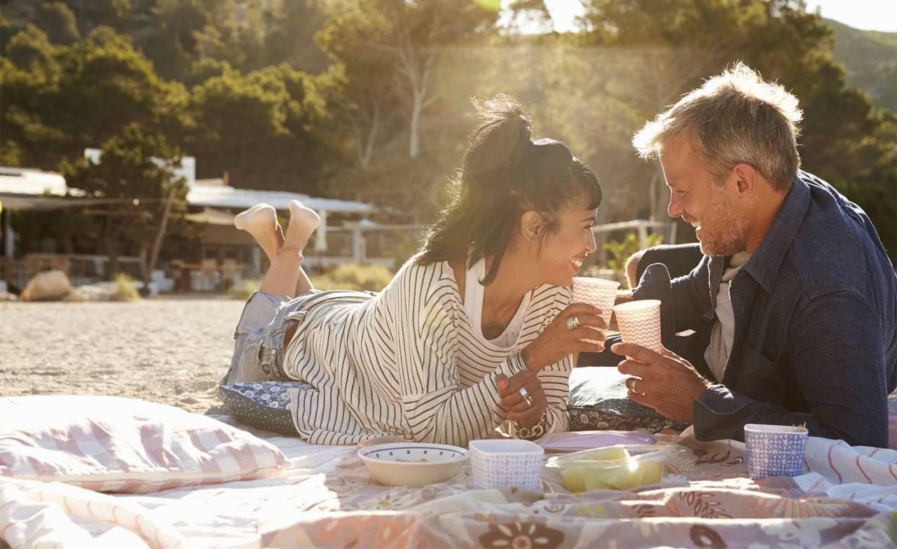 Ett kärlekspar ligger på en picknickfilt och skålar.