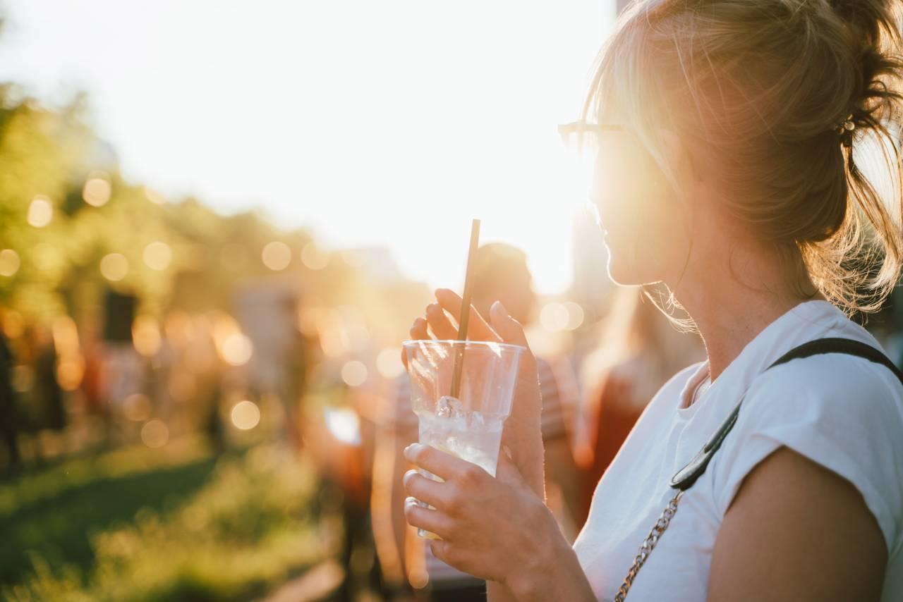 Kvinna med glas i handen blickar ut över ett folkhav