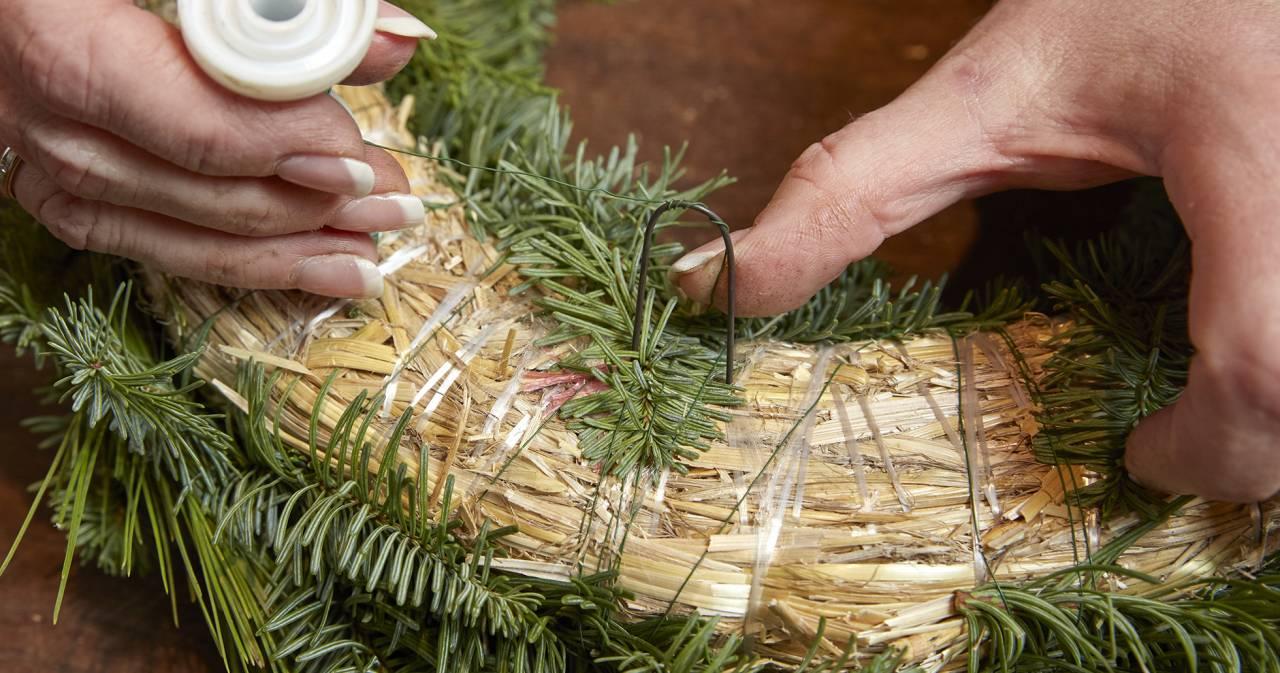 Fäst tråden i en ögla när du gör din egen gravkrans
