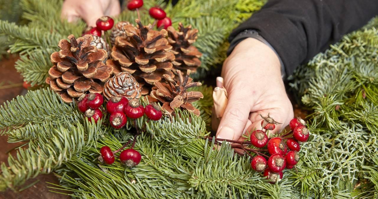 gravkrans blir dekorerad med kottar och torkade nypon