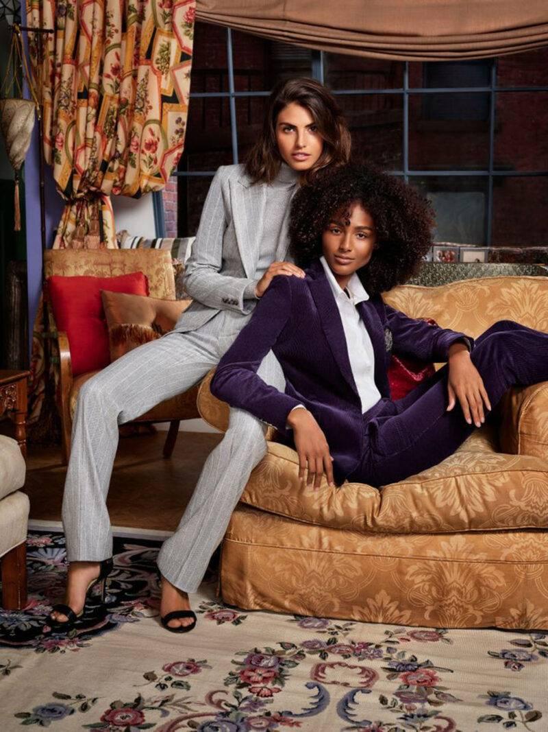 Två kvinnor i Vänner-inspirerad miljö iklädda power kostymer.