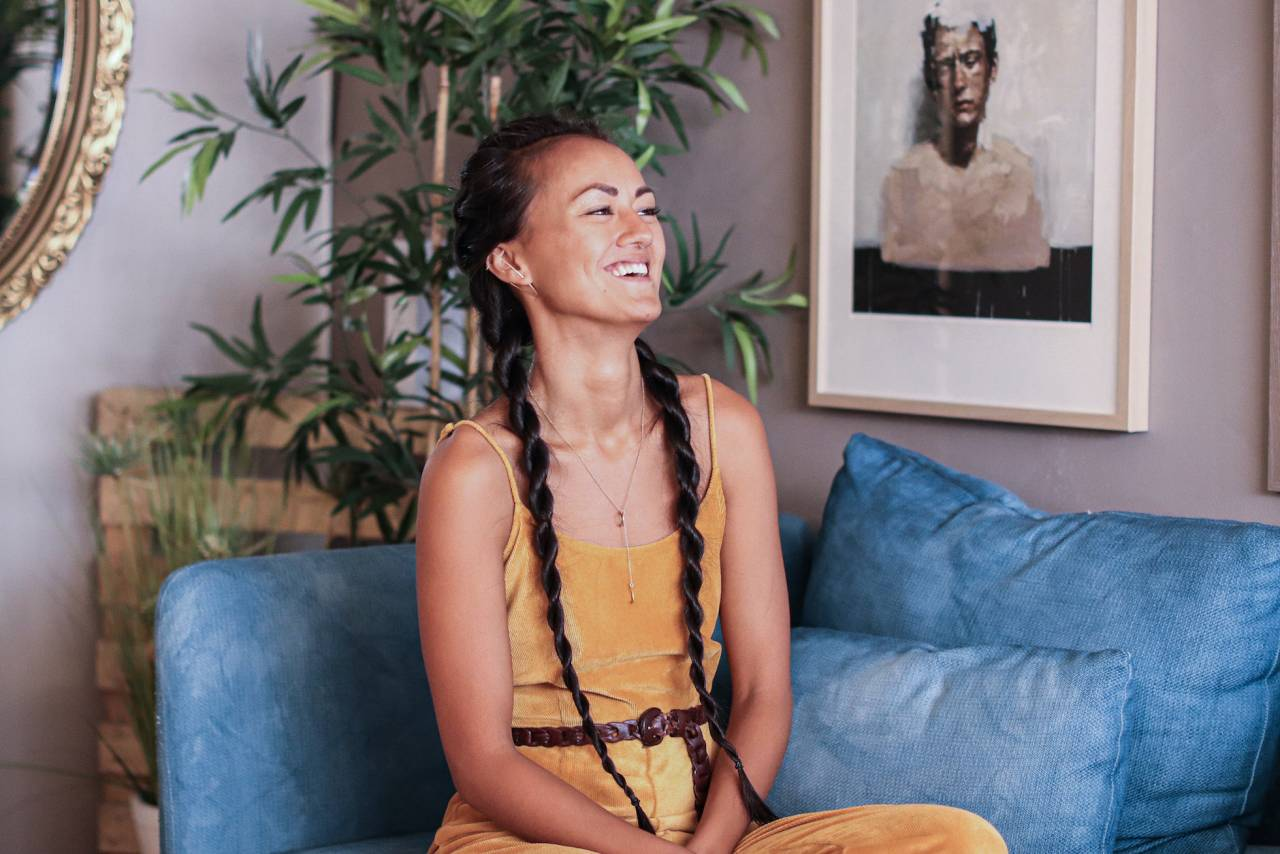 Sofia Su skrattandes i en blå soffa