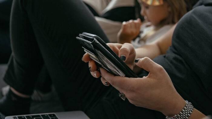Kvinna skrollar på sin telefon.