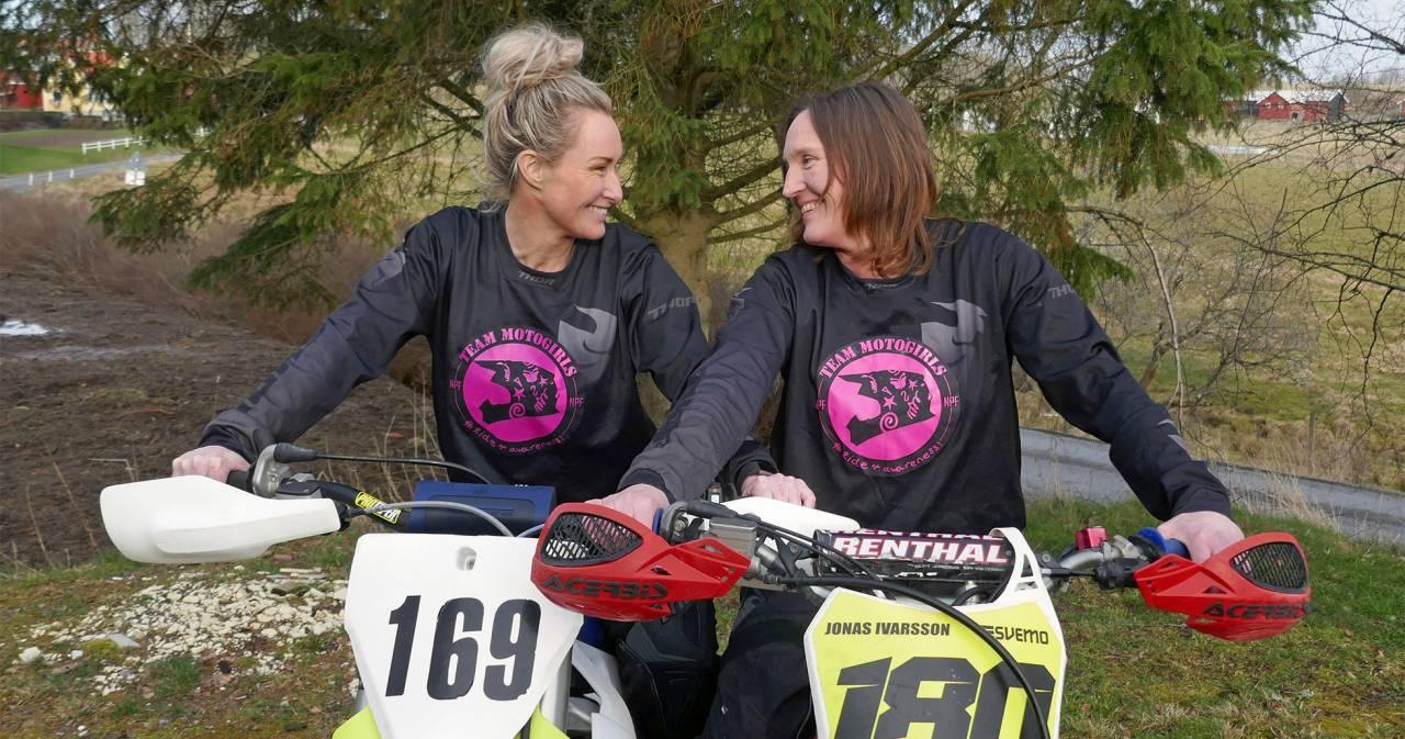 Två kvinnor sitter på varsin motocross-cykel, ler och tittar på varandra.