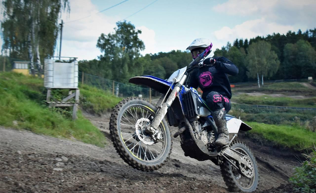 En kvinna kör motocross uppför en lerig backe.