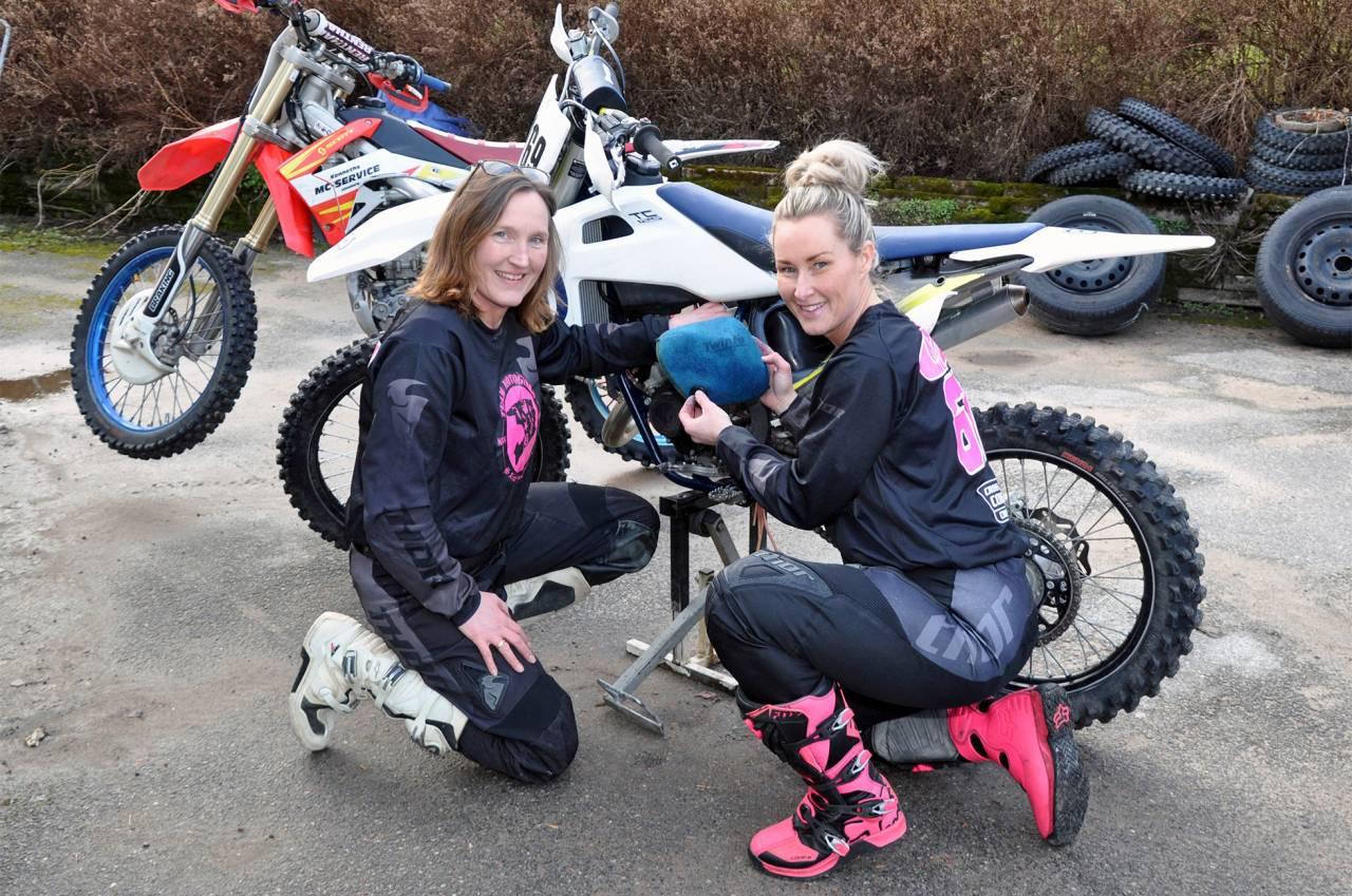Två kvinnor mekar med en motocross-cykel.