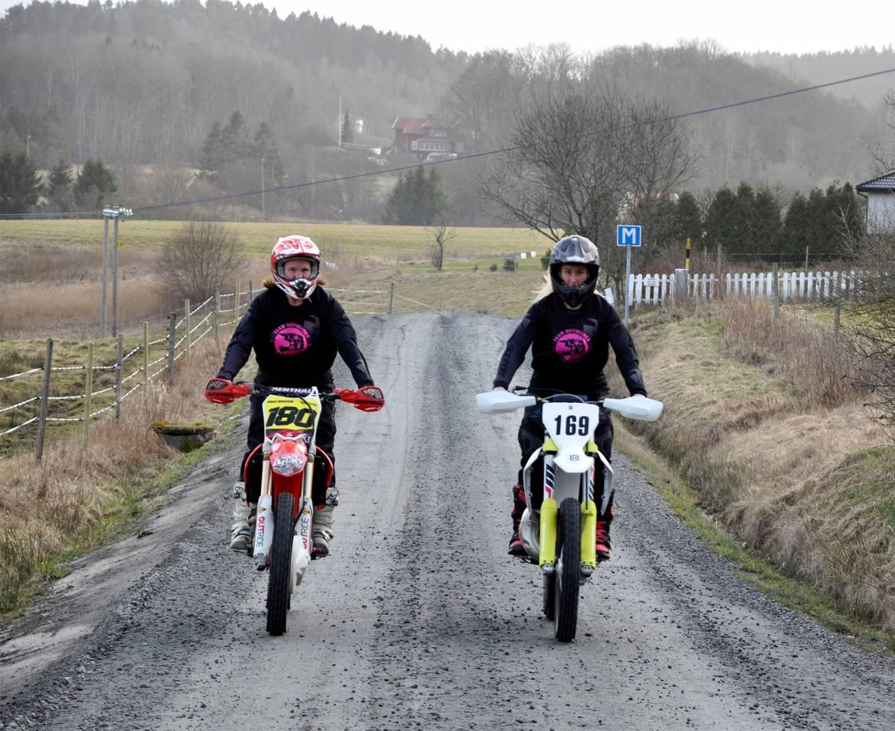 Två kvinnor kör motocross på en grusväg.