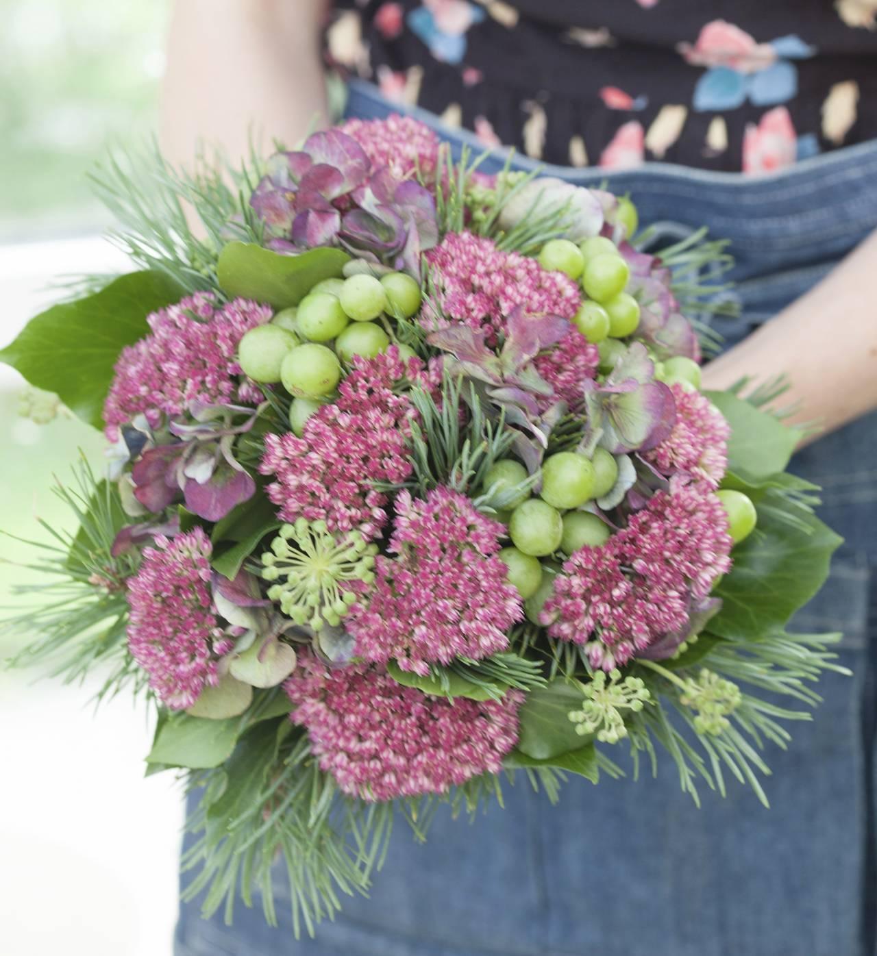 Höstbukett med röna vindruvor, kärleksört, murgrönans blommor och hortensia