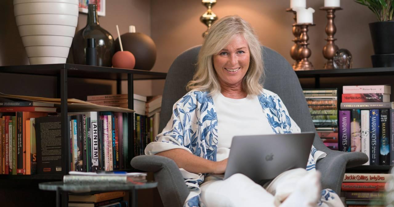Författaren Åsa Hellberg sitter i en stol med datorn i knät